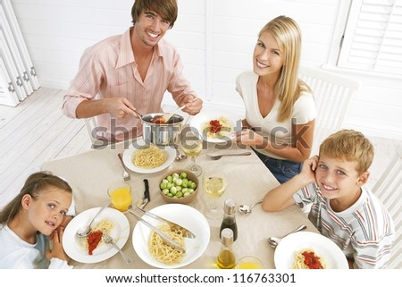 Overhead view of a young family sitting at the dining table eating spaghetti bolognaise - stock photo