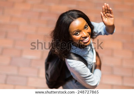 overhead view of african american student waving goodbye - stock photo