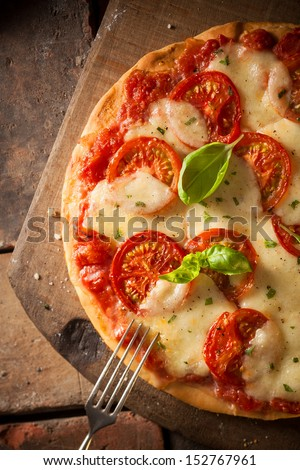 Overhead view of an appetizing tomato pizza with golden melted cheese and basil served on an old wooden board - stock photo