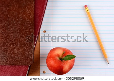 Overhead view of an apple  and pencil on notebook paper with school books. Closeup in horizontal format. Back to School concept. - stock photo