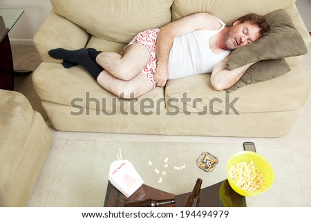 Overhead view of an unemployed man sleeping on the couch in his underwear, with food, beer, and cigarettes on the coffee table.   - stock photo