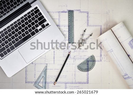 overhead view of architect's desk with blueprints and computer - stock photo