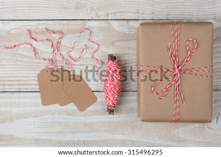 Overhead view of blank gift tags a spool of string and a plain brown paper wrapped present on a rustic whitewashed wood table.  - stock photo