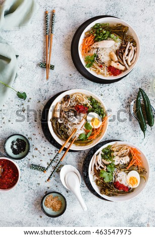 Overhead view of boat noodles in bowl with chopsticks and soup spoon. top view.