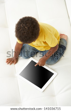 Overhead View Of Boy On Sofa Playing With Digital Tablet - stock photo