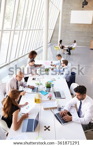 Overhead View Of Business Meeting Around Boardroom Table - stock photo