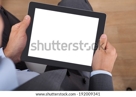 Overhead view of businessman holding digital tablet in office - stock photo