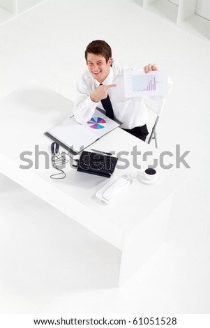 overhead view of businessman pointing at data chart - stock photo