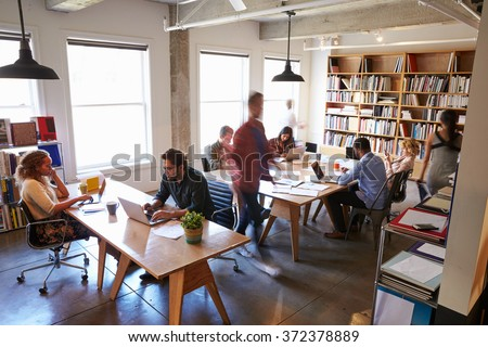 Overhead View Of Businesspeople Working At Desks In Office - stock photo