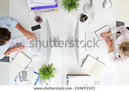 Overhead View Of Businesspeople Working At Office Computer - stock photo