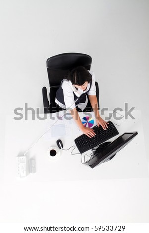 overhead view of businesswoman answering phone and working on computer - stock photo