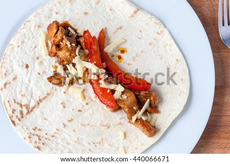 Overhead view of chicken fajita mix topped with grated cheese laying on an open flour tortilla - stock photo