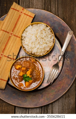 Overhead view of chicken madras served with rice. - stock photo