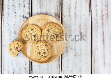 Overhead view of chocolate chip cookies on wooden tray - stock photo