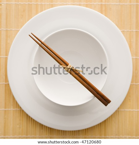 Overhead view of chopsticks lying across an empty bowl that is sitting on a plate on a bamboo mat. The dishes are white. Square shot. - stock photo