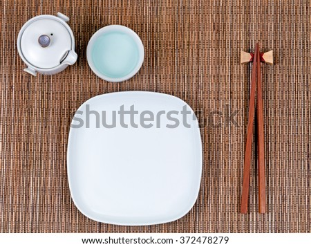 Overhead view of chopsticks, plate, cup and tea server on bamboo mat.   - stock photo
