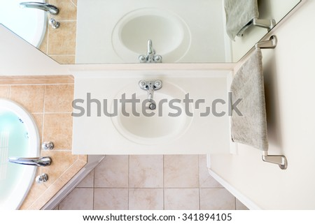 Overhead View of Classical Acrylic Top Sink along with a full bathtub and faucets - stock photo