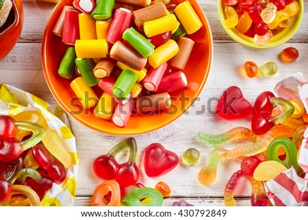 Overhead view of colorful licorice in round bowl set on rustic table next to a variety of gummy candies - stock photo
