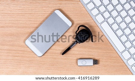 Overhead view of communication and data storage devices with computer keyboard on red oak desktop.  - stock photo