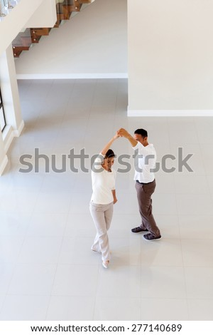 overhead view of couple dancing at their new home - stock photo