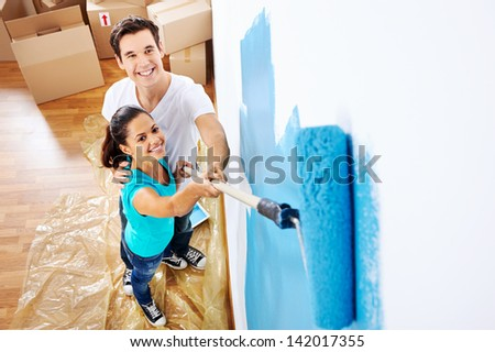 overhead view of couple having fun renovating their new home together with blue paint on a roller - stock photo