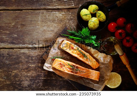 Overhead view of delicious grilled savory salmon cutlets with ingredients including a bouquet garni of fresh herbs, olive oil, tomatoes, baby potatoes and lemon on a rustic wood table with copyspace - stock photo