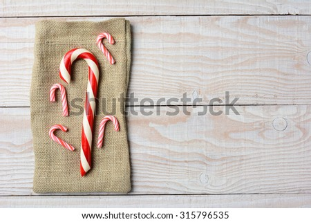 Overhead view of different sized Candy canes on a burlap bag. On a rustic wood table with copy space. - stock photo