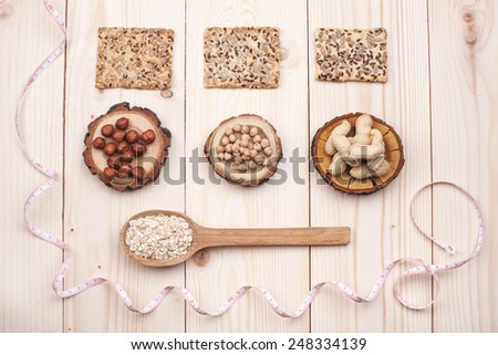Overhead view of different types of nuts and oat in wooden spoon wrapped in measure tape in diet , weight loss and healthy nutrition concept  lying on wooden table - stock photo