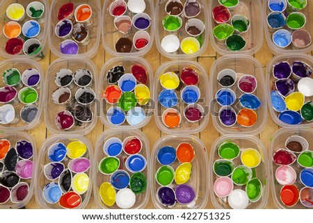 Overhead view of dozens of well used cups of vividly colored acrylic or tempera paint arranged in rows of containers. - stock photo