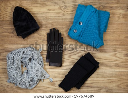 Overhead view of fall or winter clothing and accessories placed on rustic wooden boards.  Items include gloves, hat, wool socks, scarf, and sweater.  - stock photo