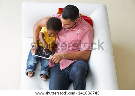 Overhead View Of Father And Son On Sofa Using Digital Tablet - stock photo