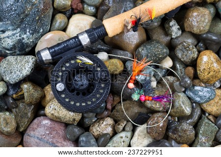 Overhead view of fishing fly reel and assorted flies on wet river bed stones - stock photo