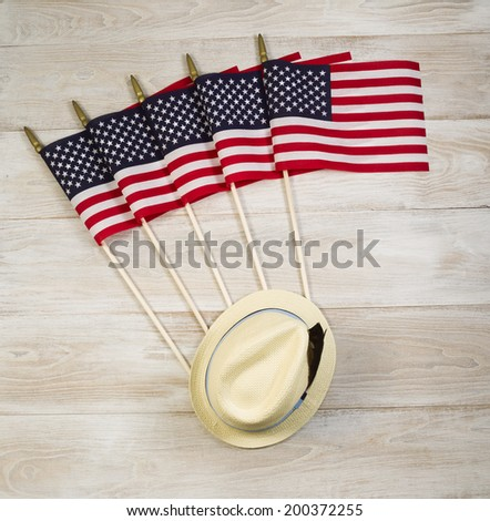Overhead view of five United States of America flags and hat placed on faded white wood.   - stock photo