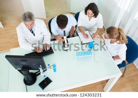 Overhead view of four laboratory technicians at work seated around a table reading and recording tests on a microscope and computer - stock photo