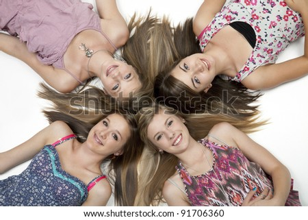 Overhead view of four teenage girls lying on white floor. - stock photo