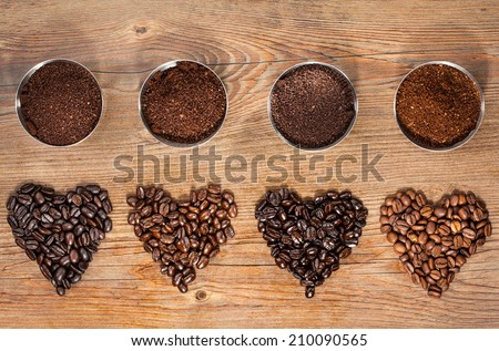 Overhead view of four varieties of roasted coffee beans in the shape of hearts with their freshly ground counterparts in small bowls on a brown wooden background - stock photo