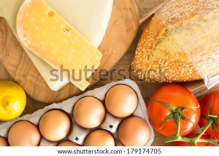 Overhead view of fresh groceries in the kitchen with a cardboard carton of free range eggs, grape tomatoes on the vine, cheese, crusty seed bread and a lemon - stock photo