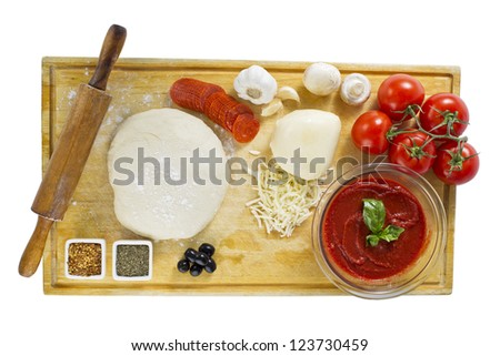 Overhead view of fresh ingredients for preparing pizza on wooden board - stock photo