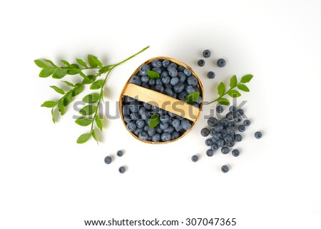 overhead view of freshly gathered blueberries in the woven  basket - stock photo
