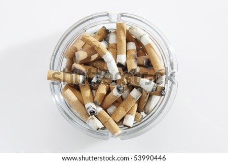 overhead view of glass ashtray full of cigarette stubs - stock photo