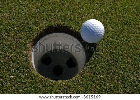 Overhead view of golf ball next to hole - stock photo
