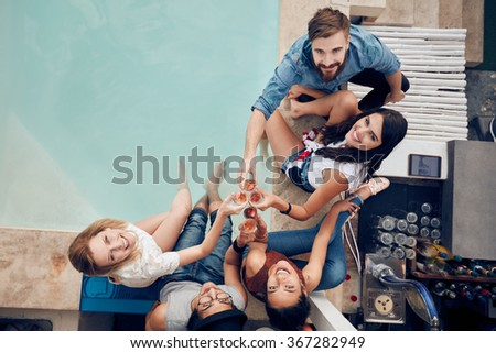 Overhead view of group of friends toasting at party by a swimming pool and looking up at camera smiling. Multiracial young people sitting by the pool having wine during party. - stock photo