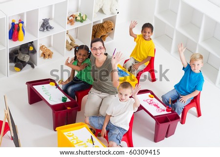 overhead view of group of preschool teacher and students in classroom - stock photo