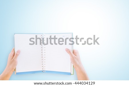 overhead view of hands holding a blank book on blue background - stock photo