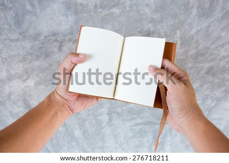 overhead view of hands holding a blank book on gray back ground - stock photo