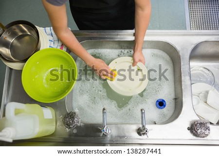 Overhead view of hands washing a plate in the sink