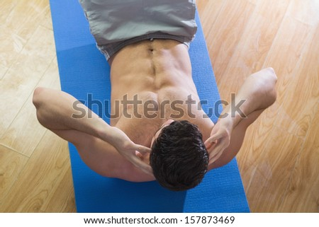 Overhead view of handsome man doing sit ups in bright living room - stock photo