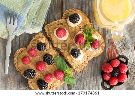 Overhead view of healthy peanut butter sandwiches on wholewheat bread topped with fresh raspberries and blackberries, herbs and mozzarella cheese on a wooden picnic table with a jug of orange juice - stock photo