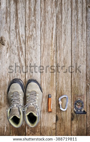 overhead view of hiking boots, knife, and compass - stock photo