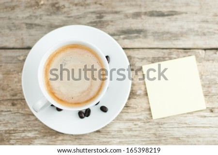 Overhead view of hot coffee drink with hand and sticky note with pencil - stock photo